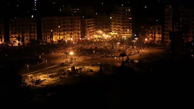 Exterior nigh shots from balcony looking across to Tahir Square with large crowds gathered Exterior night shots tanks on the streets Exterior night...