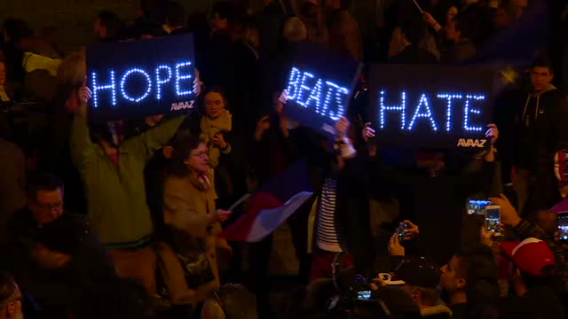 Exterior night shot of Emmanuel Macron supporters gathered at his victory rally at the Pyramide de Louvre some of them holding a light banner reading...
