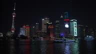Exterior night shot Shanghai skyline and Oriental Pearl Tower illuminated against the night sky with passenger ferries passing along river on...