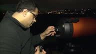 exterior night shots Astronomer setting up telescope Astronomer Setting Up Telescope on February 15 2013 in London England