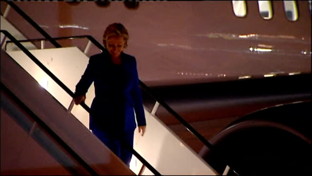 Exterior night shots Hillary Clinton US Secretary of State steps down plane at Heathrow Airport greets people and walks to airport building on...