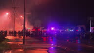 Exterior night shots of a line of riot police facing towards a cloud of tear gas and unseen protesters in the distance>> on August 17 2014 in...