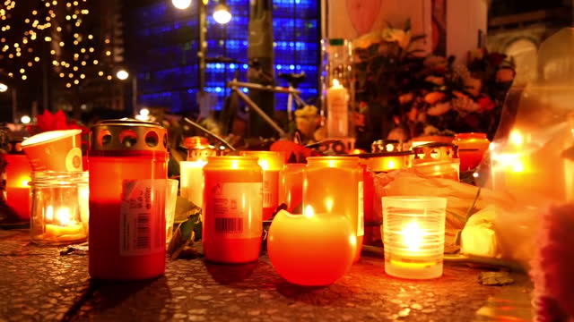 Exterior night shots of candles lit at memorial for Berlin Christmas market victims and shots of emergency services personnel paying respects on...