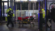 Exterior night shots of injured people being wheeled to ambulances by paramedics and fire fighters on a mobile crane inspecting the roof of the...