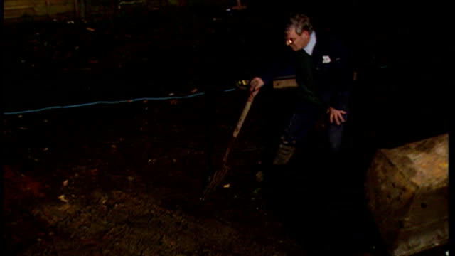 Exterior night shots of investigators digging and carrying out ground penetrating radar survey of ground next to Fred and Rosemary West's garden at...
