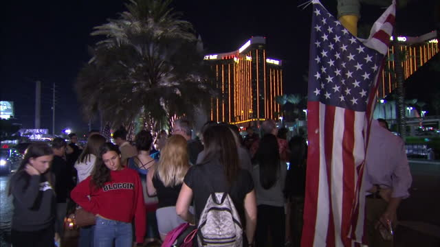 Exterior night shots of people looking at tributes to the victims of the Las Vegas mass shooting attack including shots with the Mandalay Bay Hotel...