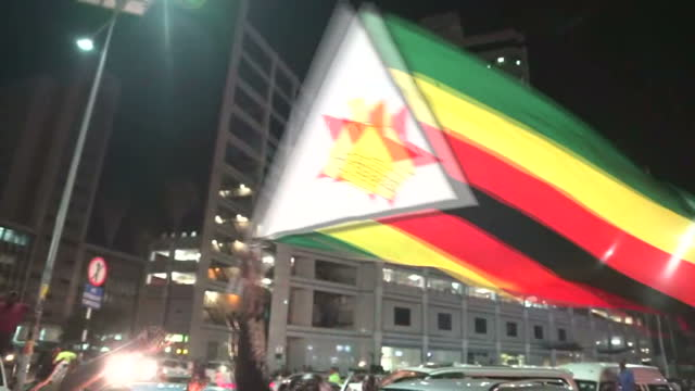 Exterior night shots of people taking part in street celebrations singing dancing and waving flags following the announcement that Robert Mugabe is...