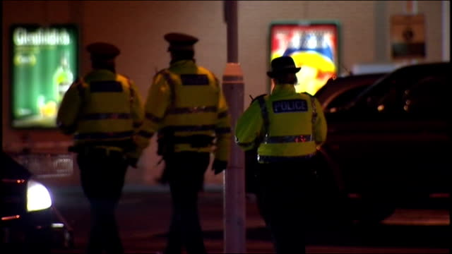 Exterior night shots of police gathered in Asda car park in Robroyston Glasgow area speaking to people witness's and forensic team at scene of...