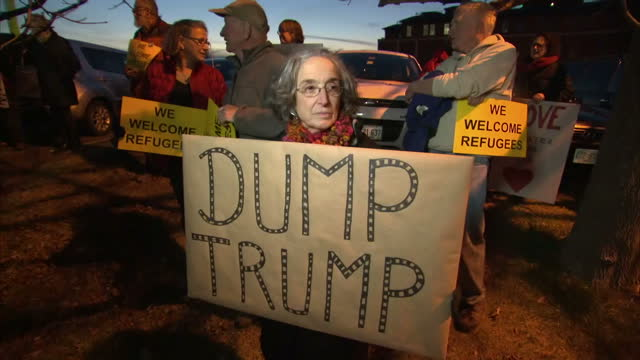 Exterior night shots of protesters holding up signs against Donald Trump such as 'Dump Trump' and 'Choose Love' on December 10 2015 in Portsmouth New...