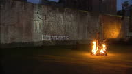 Exterior night shots of the Tower of London illuminated by bonfires and projected animations of the Game of Thrones logo being set alight by...