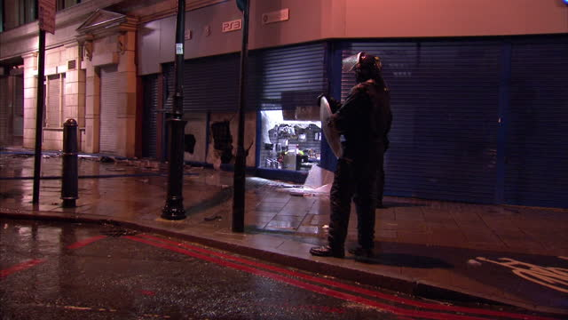 Exterior night shots riot police officer stands guard outside ravaged electrical store with shattered windows Exterior night shots riot police block...