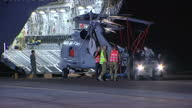 Exterior night shots Seahawk helicopter being unloaded from RAAF C17 Globemaster transporter plane on 28 March 2014 near Perth Australia
