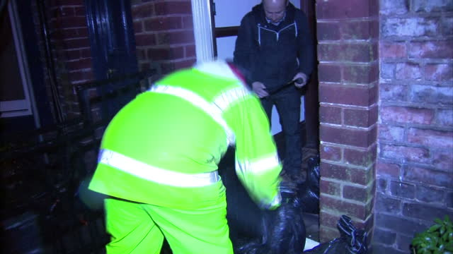 exterior night shots workmen piling sandbags next to wall of house on residential street Flood Preparations in Darlington on November 26 2012 in...
