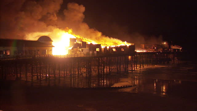 Exterior nightshots Hastings Pier on fire with the structure engulfed by flames Exterior nightshots firefighters crane rising above the pier Exterior...