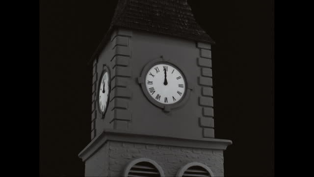 MS Exterior of clock tower with clock face at night / United States