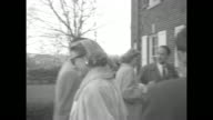 WS exterior of Grace Kelly house in Philadelphia press in driveway / Kelly with sunglasses and fur on walks with others toward door of house Prince...