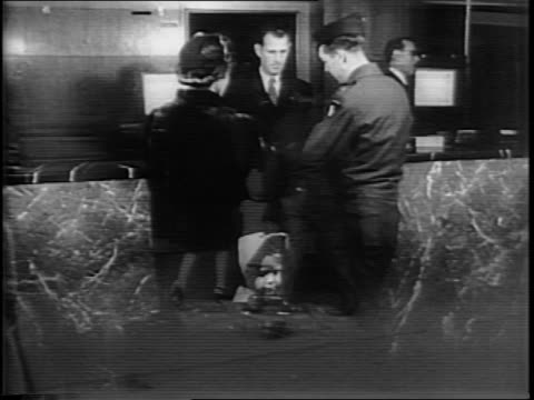 Exterior of Hotel Pennsylvania in New York City / Captain Frank L Lillyman and family carry luggage to hotel entrance / Lillyman at hotel lobby desk...
