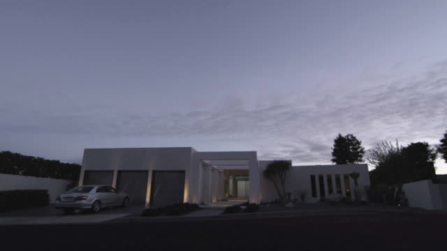 WS Exterior of modern house with car parked in driveway at dusk