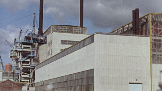 1969 MONTAGE Exterior of nuclear reactors, the last one connected to the power grid / United Kingdom