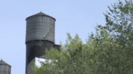 MS Exterior of shingled water tower through the treetops