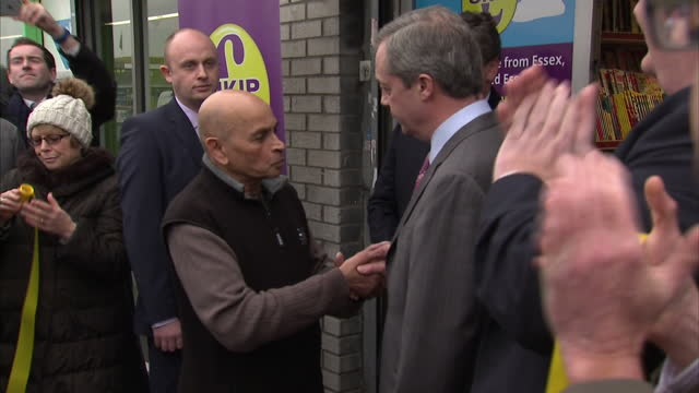 Exterior of UKIP leader Nigel Farage outside newsagents cutting yellow tape shaking hands with man and smiling on February 12 2015 in Canvey Island...