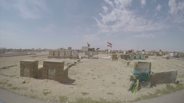 Exterior point of view shots driving past gravestones of Shia Muslim fighters buried at Wadi AlSalaam cemetery on March 21 2015 in Najaf Iraq