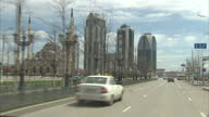 Exterior point of view shots driving through streets of Grozny Grozny street scenes passing Mosque in Grozny Grozny skyscrapers on April 16 2015 in...