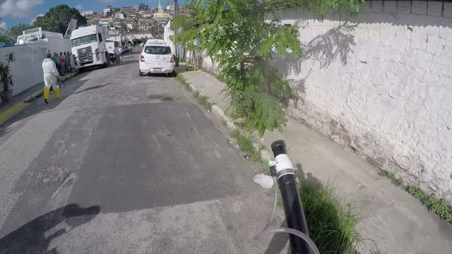 Exterior point of view shots of a council worker in Recife fumigating against mosquitoes walking through a residential area spraying houses vehicles...