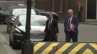 Exterior shot Alun Cairns MP and Patrick McLoughlin walk together down Downing Street and out along Whitehall in London England on Tuesday 14th March...