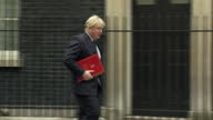 Exterior shot Boris Johnson Conservative MP walks into 10 Downing Street holding red book greets media in London England on Tuesday 14th March 2017