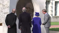 Exterior shot Her Majesty The Queen and Prince Phillip Duke of Edinburgh take a closer look at war memorial sculpture talking to artist Paul Day and...