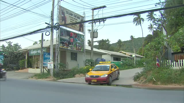 Exterior shot of a Koh Samui street with advertising for Island Safari and Elephant trecking locals going about on cars and motorbikes on February 02...