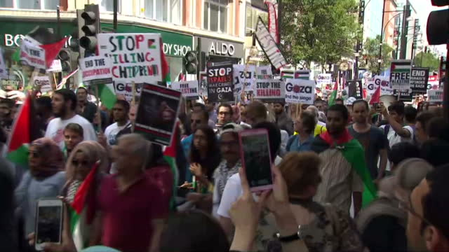 Exterior shot of crowds of proPalestinian protesters marching along Oxford Street chanting and carrying placards and flags>> on August 09 2014 in...