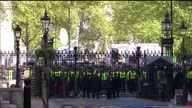 exterior shot of London Eye pan down to a long shot of anticonservative protesters behind police lined gates of Downing Street with banners and...