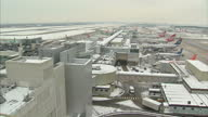Exterior shot of plane coming in to land in snowy conditions Exterior shots of Qatar airways plane taxiing along tarmac Exterior wide shot of snowy...