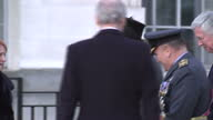 Exterior shot pan from war sculpture to Prime Minister Theresa May talking to artist Paul Day walks away wearing hat followed by Michael Fallon...