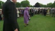 Exterior shot Queen Elizabeth II walks past line of guests at Buckingham Palace garden party and briefly stops to talk to guide dog owner on May 22...