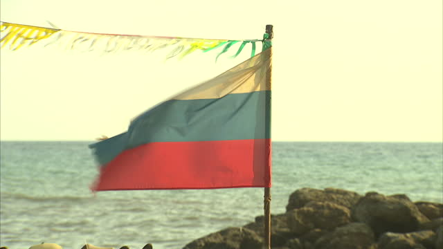 Exterior shot showing torn and damaged Union Jack and Russian flags blowing in the wind with the sea in the background on September 07 2014 in Paphos...