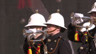 Exterior shot still marching band stood as trumpet player plays at war memorial honoured the service and duty of both the UK Armed Forces and...