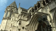 Exterior shot wide of The Royal Courts of Justice building sign and crest on building on bright sunny weather blue skies day in London England on...