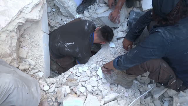 Exterior shots a man moving debris off crying girl who is trapped under rubble in the aftermath of an airstrike on September 23 2016 in Bab alNairab...