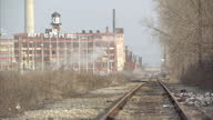 Exterior shots abandoned factory building with overgrown railway running past factory building which is covered in graffiti Old water tower can be...