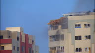 GAZA exterior shots air strike/rocket explosive hits tower block plume of smoke and dust billows from building as debris falls