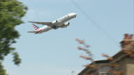 Exterior shots American Airlines passenger plane taking off from Heathrow airport flying low over residential houses on flight path on July 01 2015...