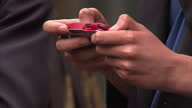 Exterior shots anonymous hands of teenagers using phones gadgets in school playground and school classroom Children in classroom using mobile phones...