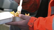 Exterior shots anonymous people eating fish and chips on sea front on January 20 2016 in WellsnexttheSea England