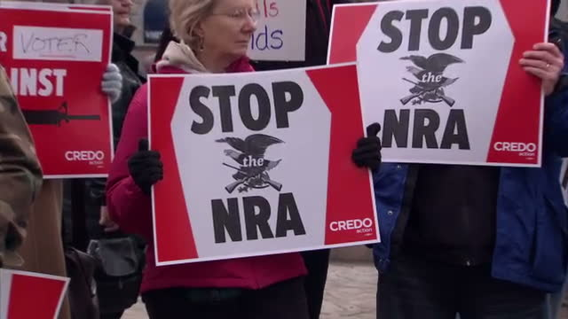 Exterior shots antiNRA protesters demonstrate vocally with placards banners calling for gun control a tougher stance on the NRA AntiNRA Protesters...