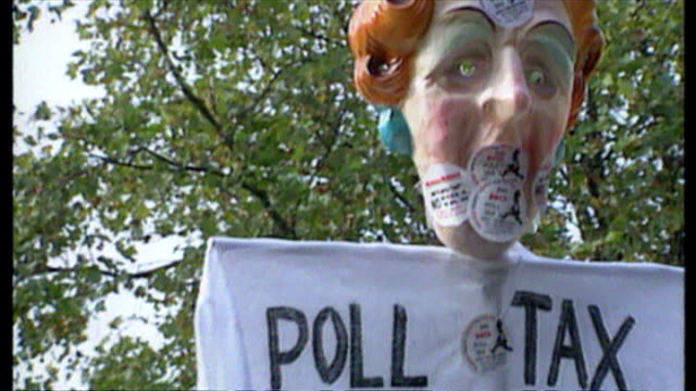 Exterior shots AntiPoll Tax protester holding mask of Margaret Thatcher on stick with tshirt saying 'Poll Tax Maggies Gift To The Rich' on October 20...