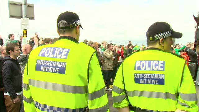 Exterior shots AntiSectarian Initiative police wearing high visibility jackets marshall large crowds of chanting Celtic supporters outside Celtic...