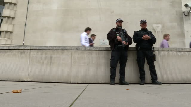 Exterior shots Armed Police stood guard by entrance to New Scotland Yard / Exterior shots armed police officers walking / exterior shots two armed...